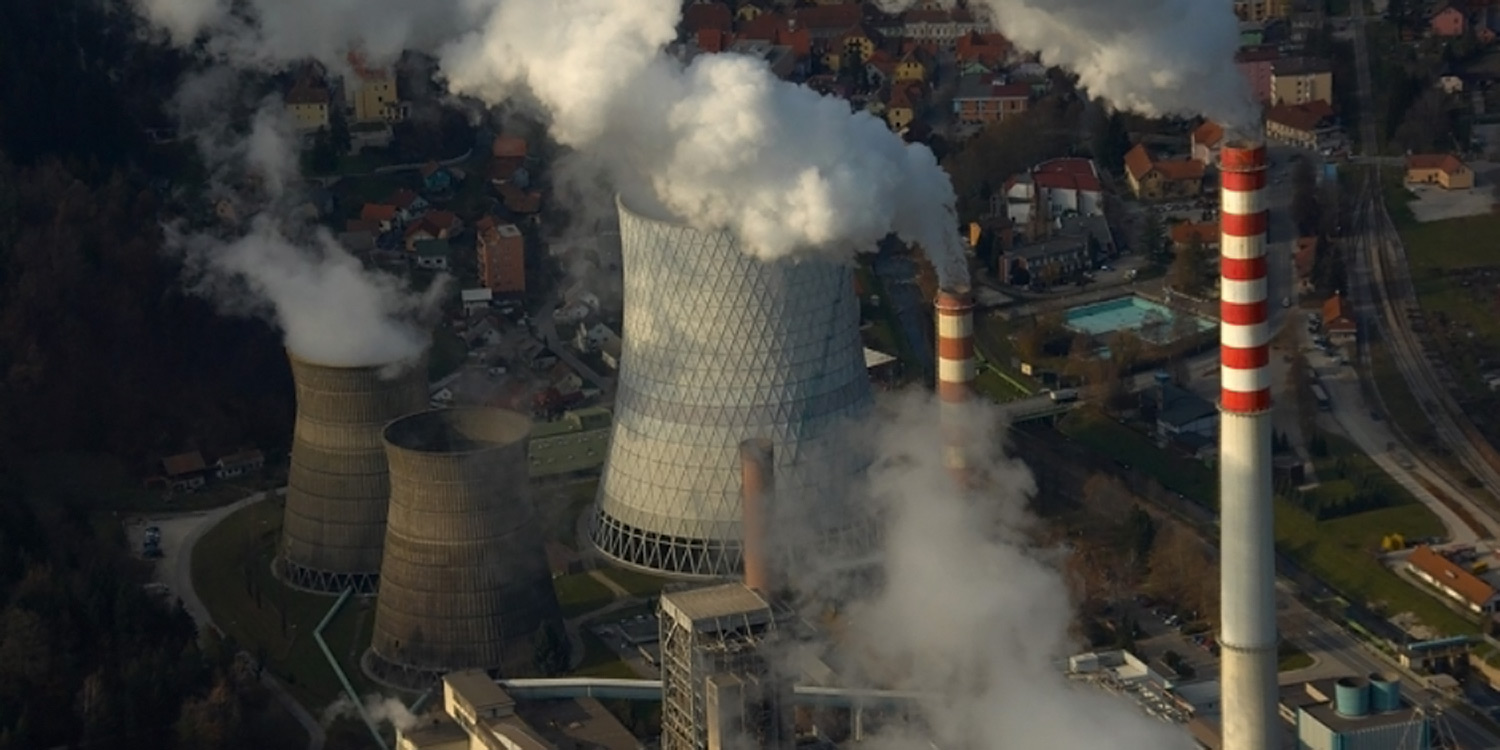 An aerial view of the Sostanj lignite power plant showing smoke stacks and cooling towers and lots of smoke and steam.