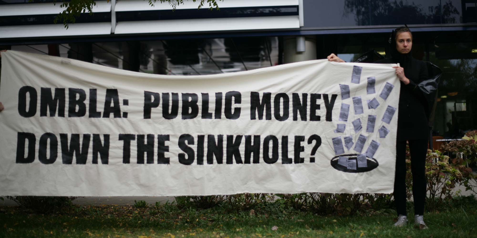 "A young woman holding a banner that reads ""Ombla: public money down the sinkhole?"""