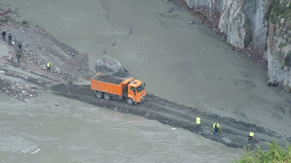 An aerial view of a truck driving through a valley full of grey mud.