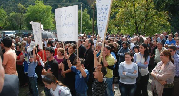 People shouting and protesting with placards with Georgian letters.