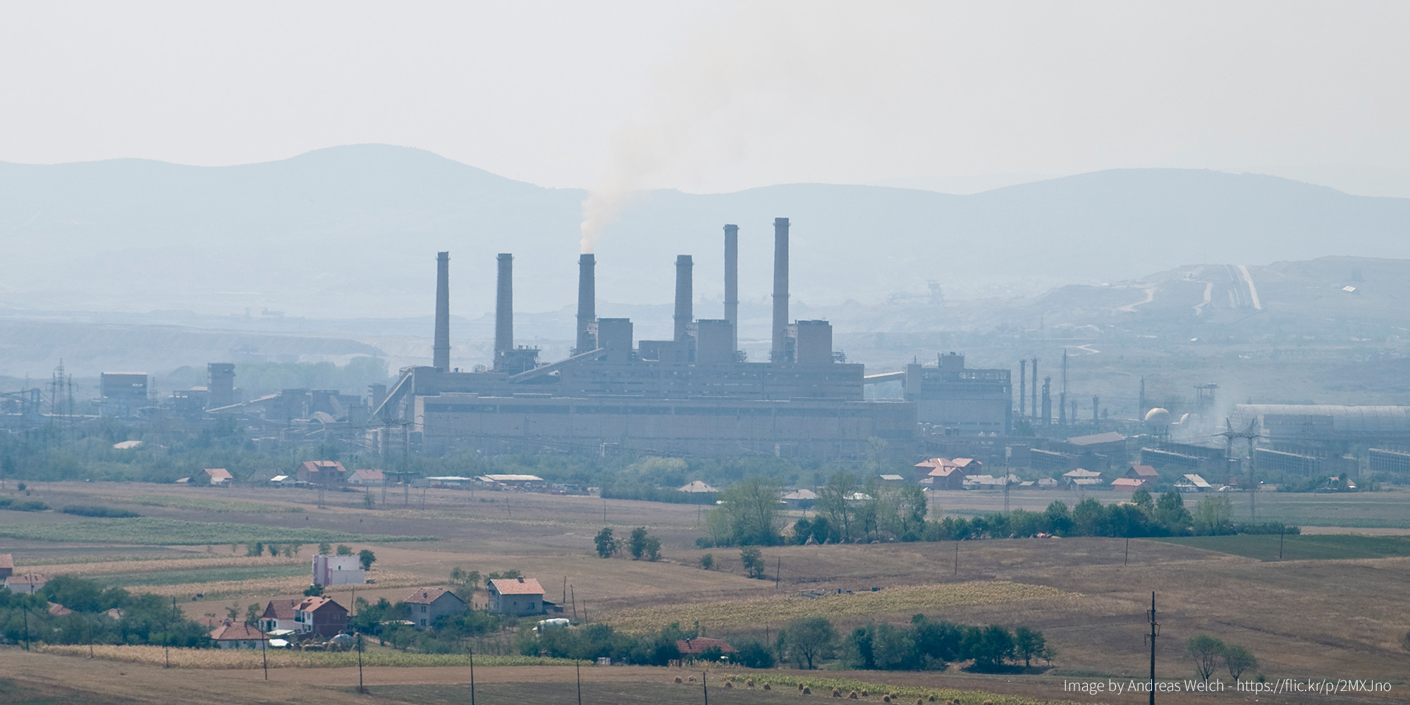 A coal power plant with 3 smoke stacks surrounded by settlements, all seen from a distance.