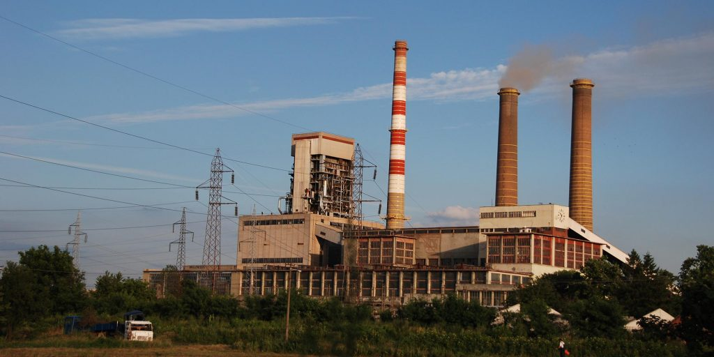 The Kolubara A coal power plant in Serbia. Three smoke stacks and a power house are seen in front of a blue sky.