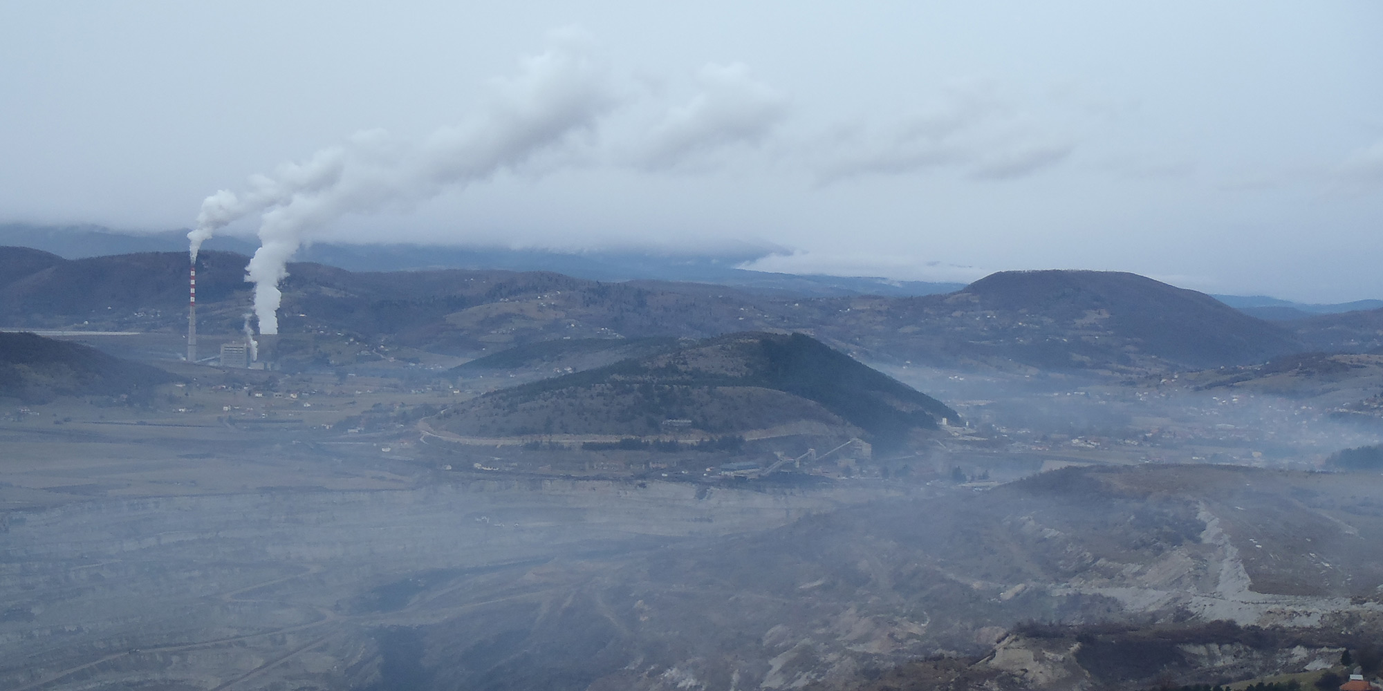 Panorama view of a valley that is dominated by a coal power plant. The smoke from the power plant's stacks fills the entire valley.
