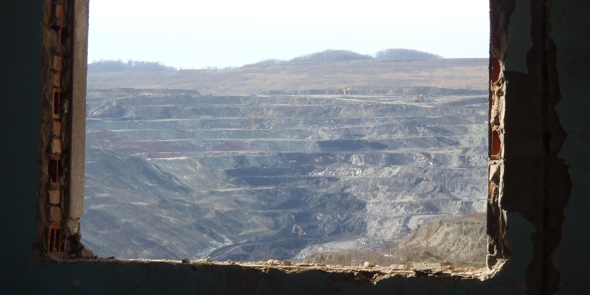 An open pit mine seen through the window of a demolished building.