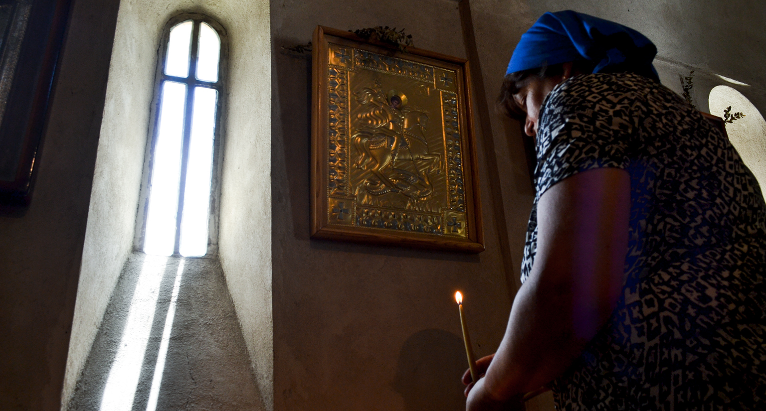 A woman lighting a candle in a church.