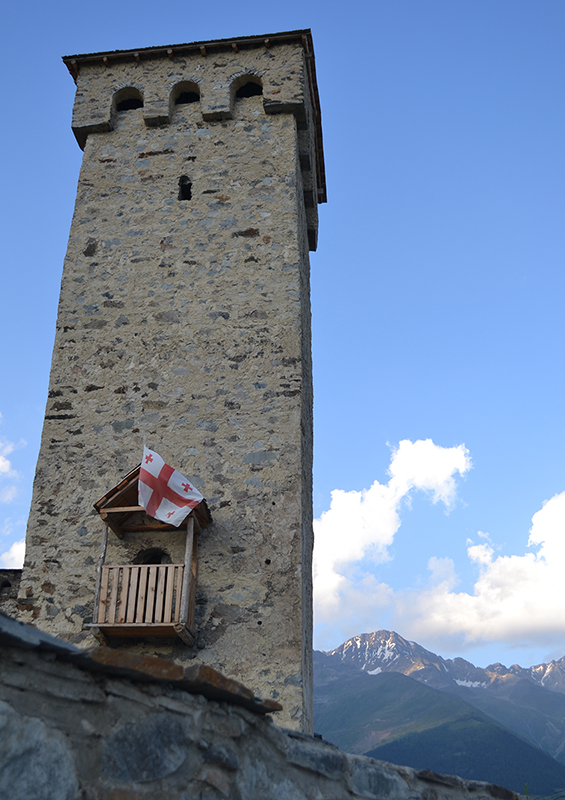 A large medieval stone tower in front of a mountain range. A Georgian flag is hanging on its side.