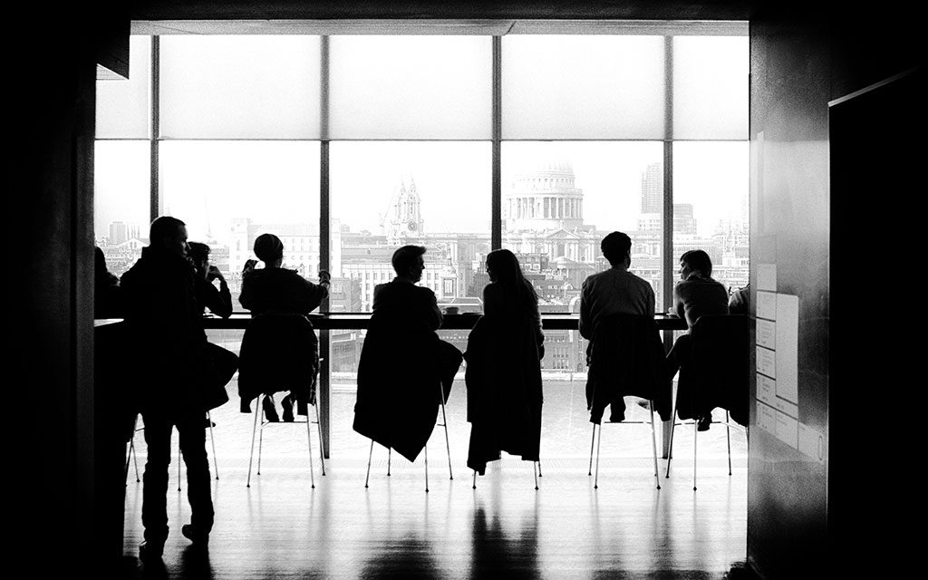 Silhouettes of about ten people sitting on chairs in front of a large window.