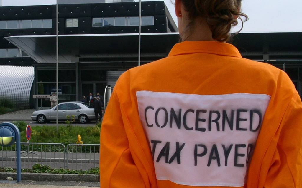 "A person in a workers overall seen from behind with the words ""concerned tax payer"" printed on the back."