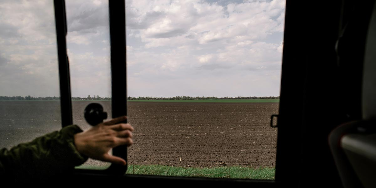 A view of fields through a train window. A hand is holding the window open.