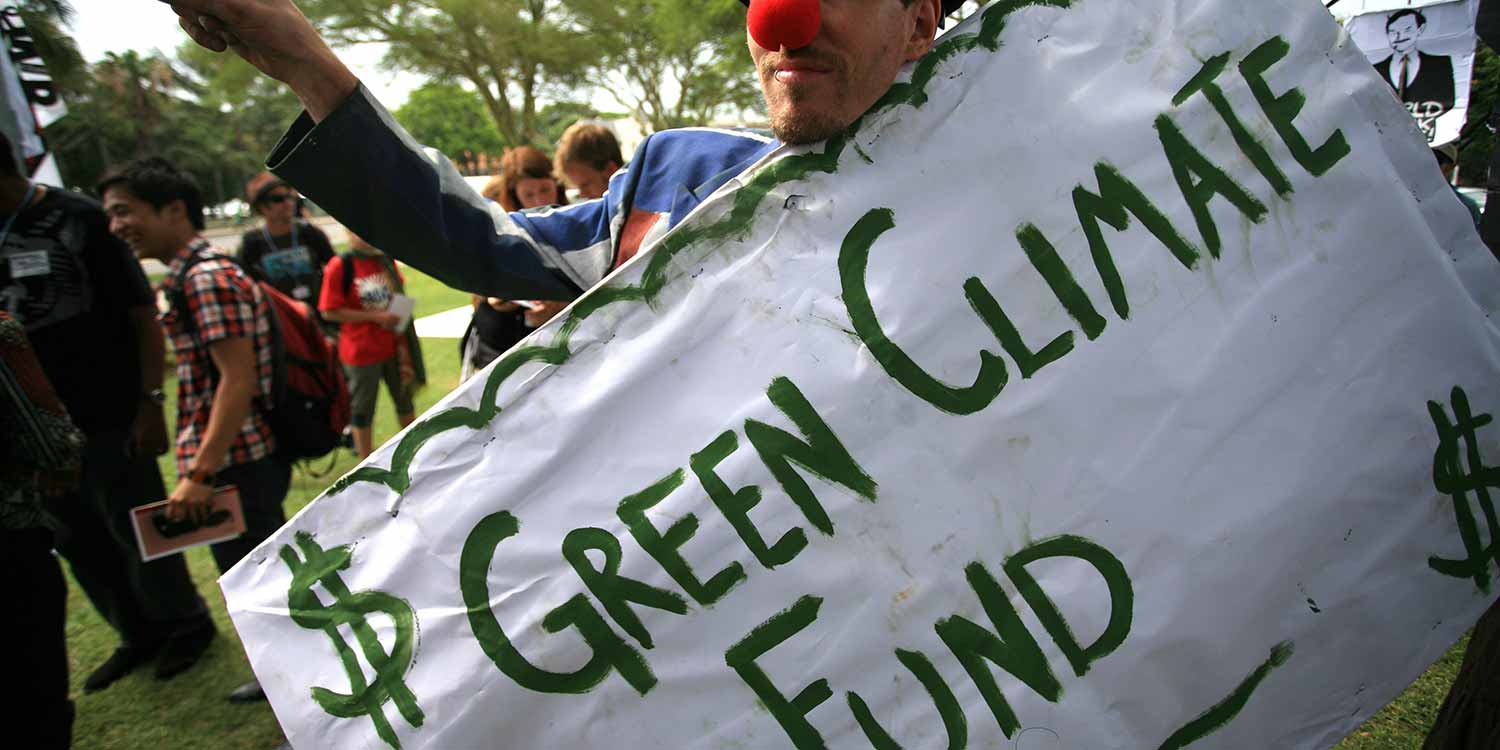 "A person with a clown's nose holding a banner with the text ""$ Green Climate Fund"""