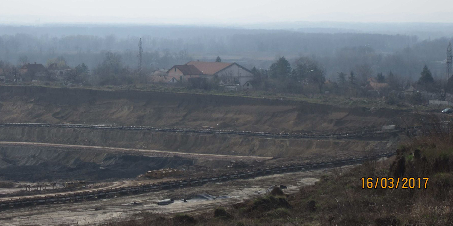 Family houses in the background have almost been reached by an open pit mine.
