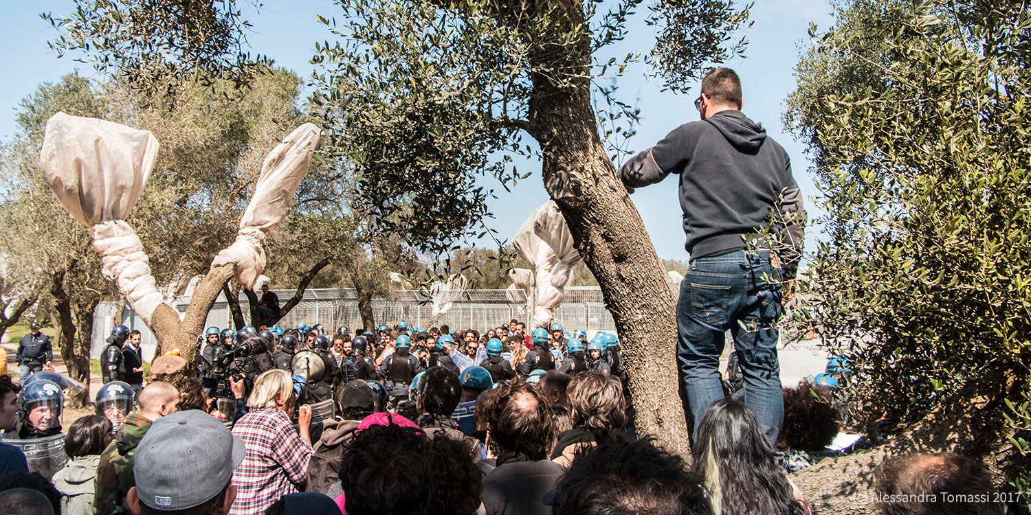 A crowd of residents in the front facing police forces in the background with trees standing across the scene.