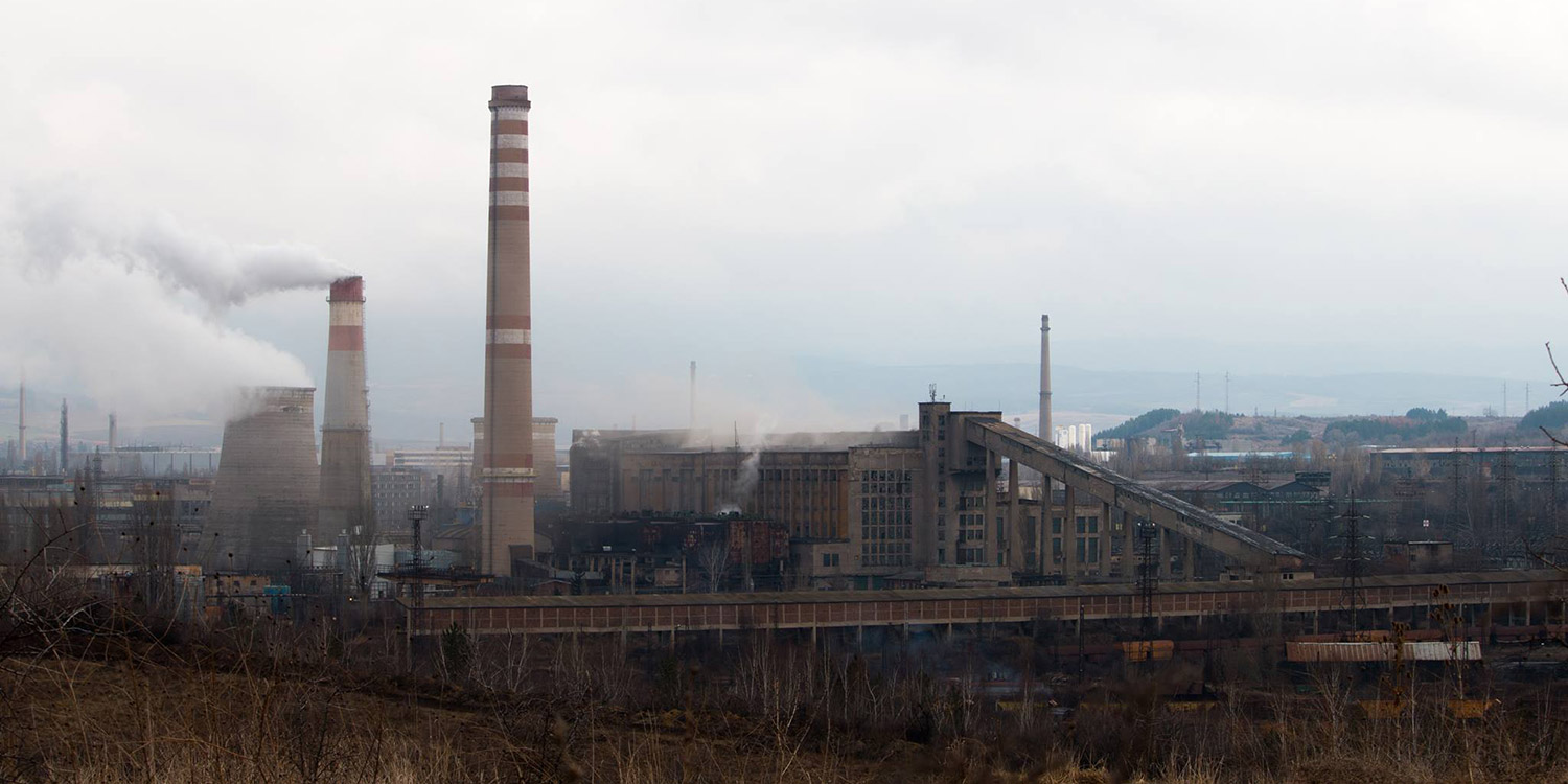 The smokestacks of the Penrik coal power plant. are visible against a town submerged in smog.