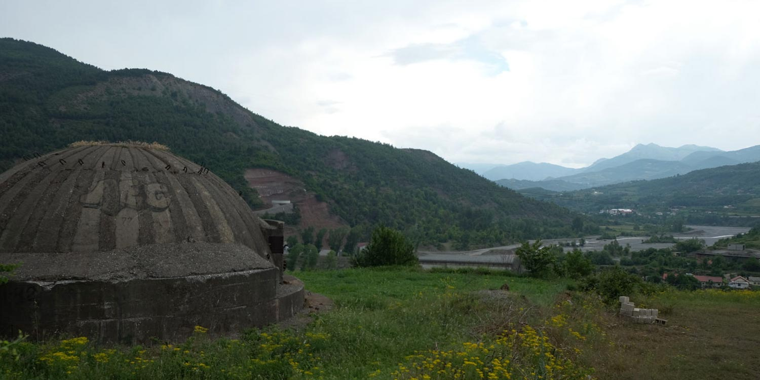 A bunker in front of a mountain panorama in Albania.
