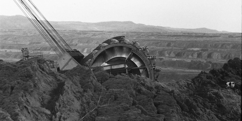 An excavator half hidden behind a dirt hill.