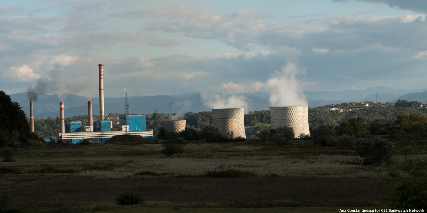 In a panorama view smoke and steam is coming out of the towers of a coal power plant.