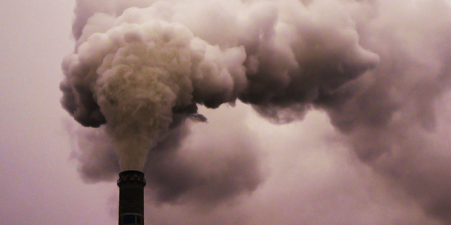 A smoke stack of a coal power plant letting off a big cloud of smoke, seen as close-up.