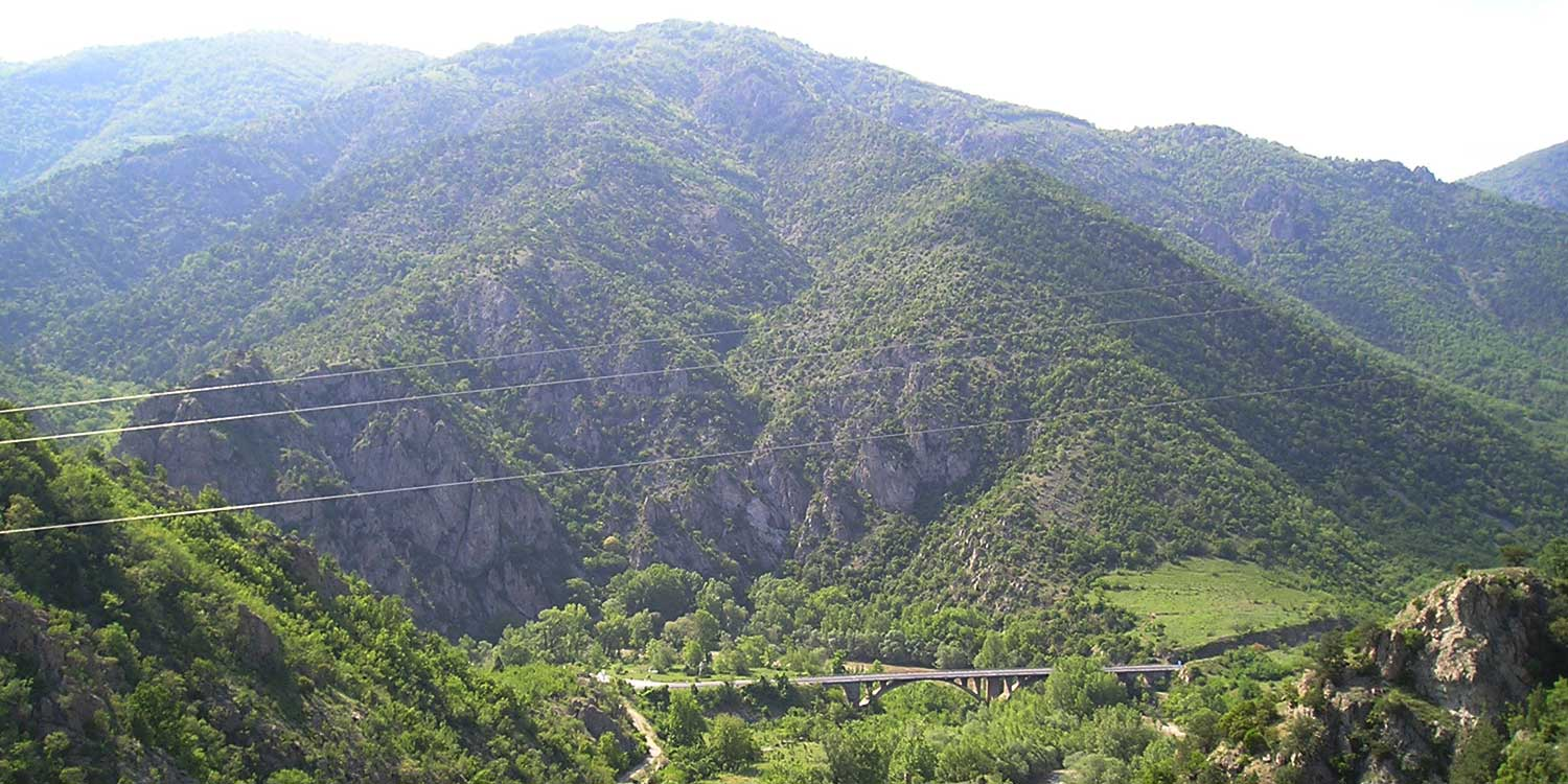 A panorama shot of the Kresna gorge, a wide, green valley between mountains full of vegetation.