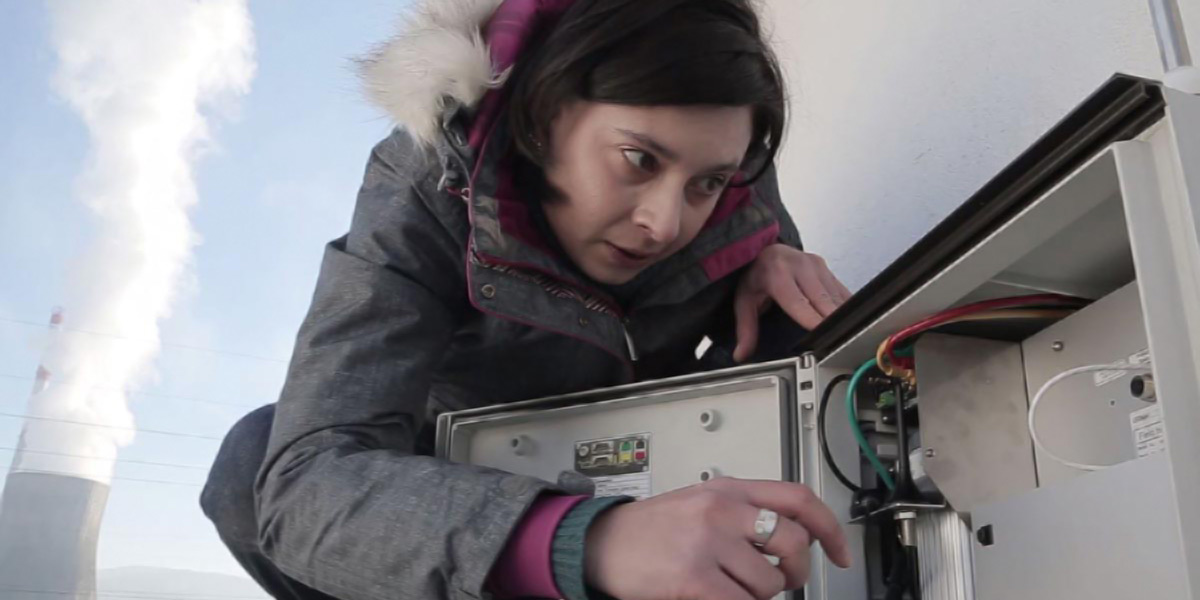 A person leaning over a pollution monitoring device, apparently setting it up.