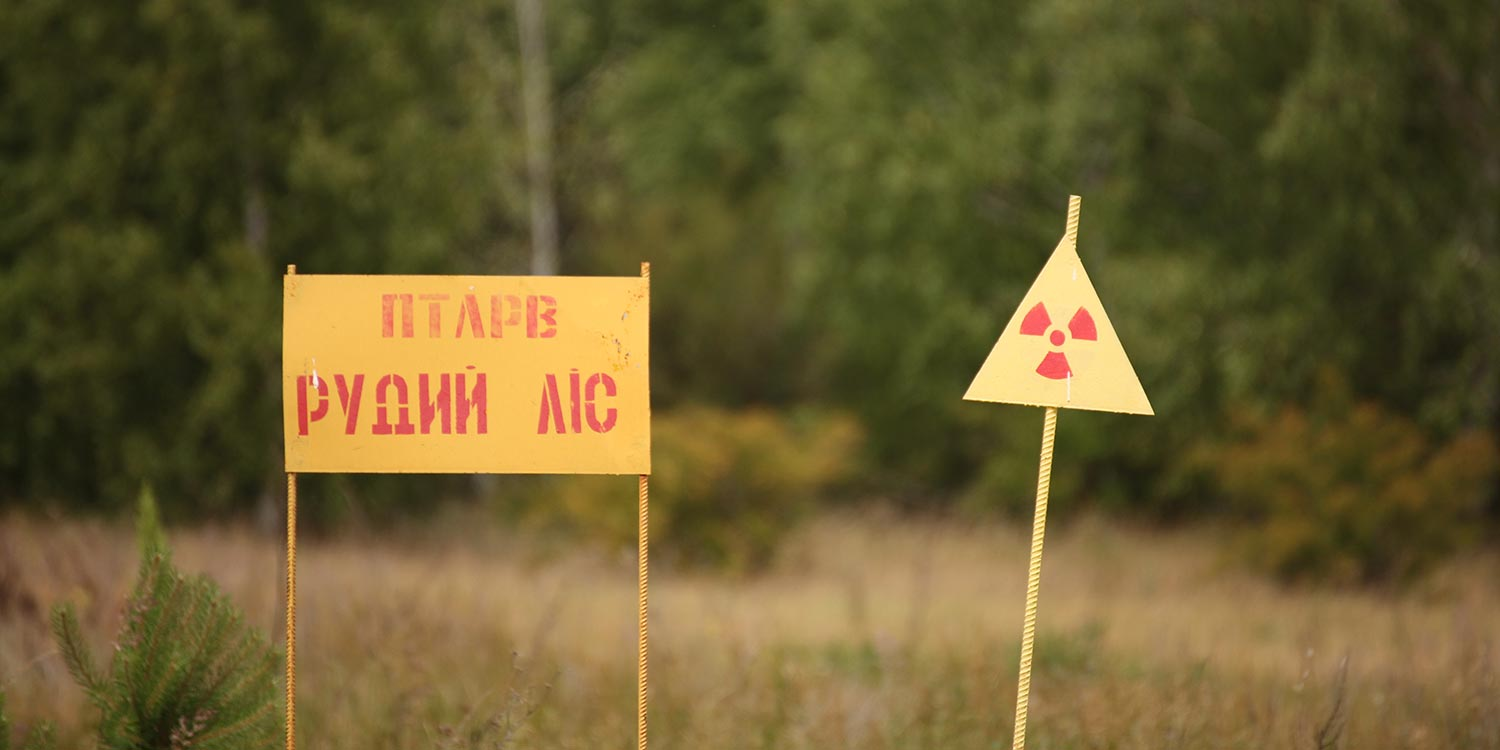Two warning signs about nuclear danger. One with Ukrainian letters.