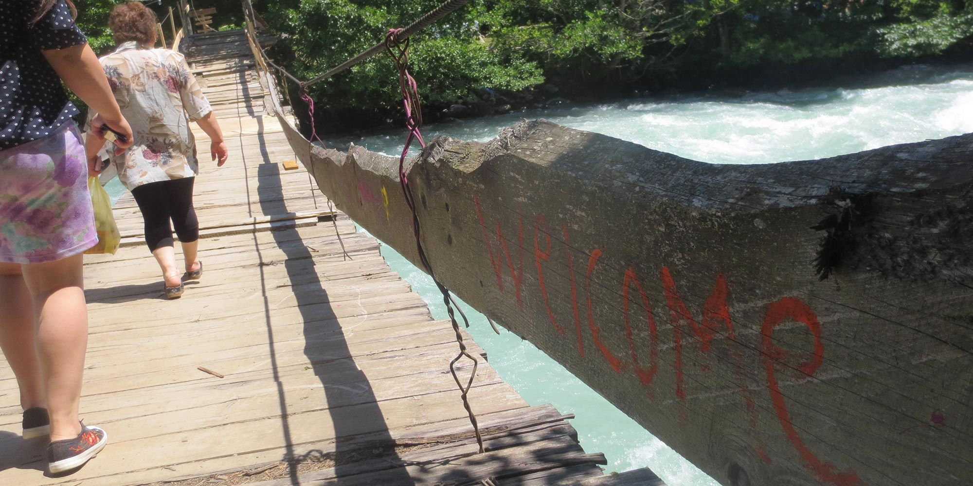 A wooden hanging bridge over a strong river stream. The word welcome is written in red letters on the bridge.