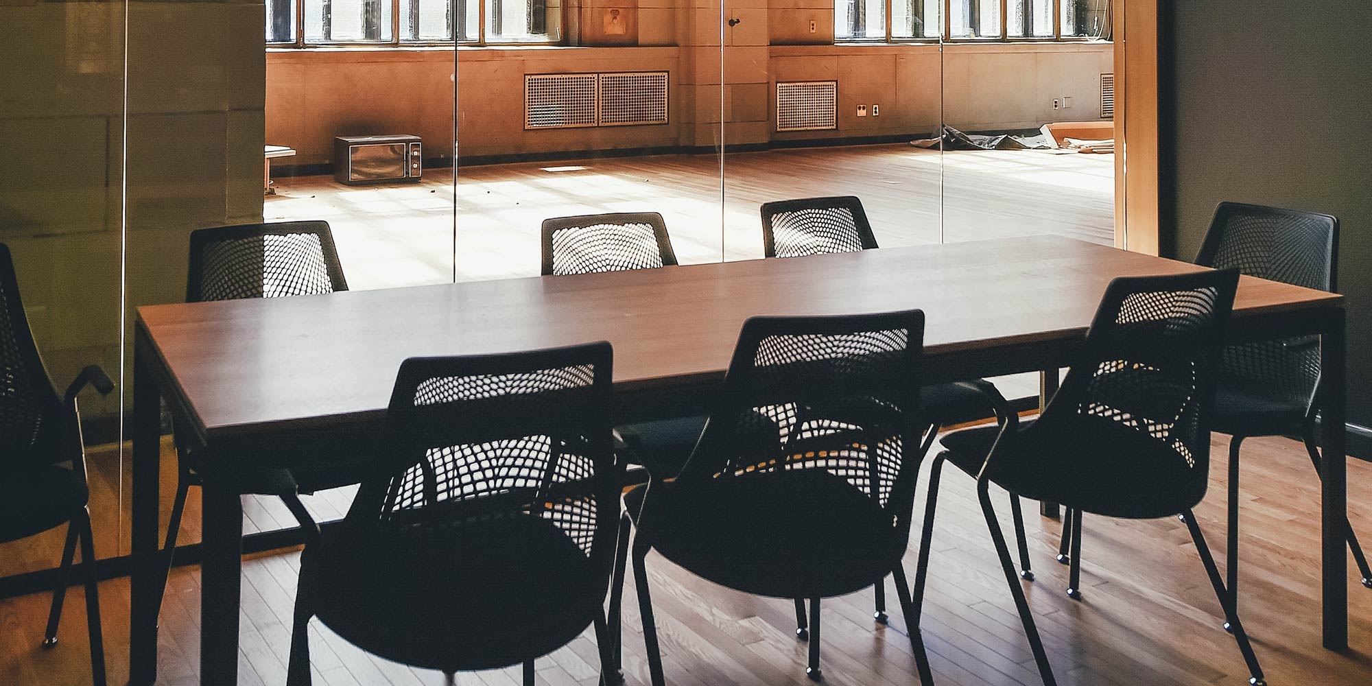 A meeting room with empty chairs around a table.