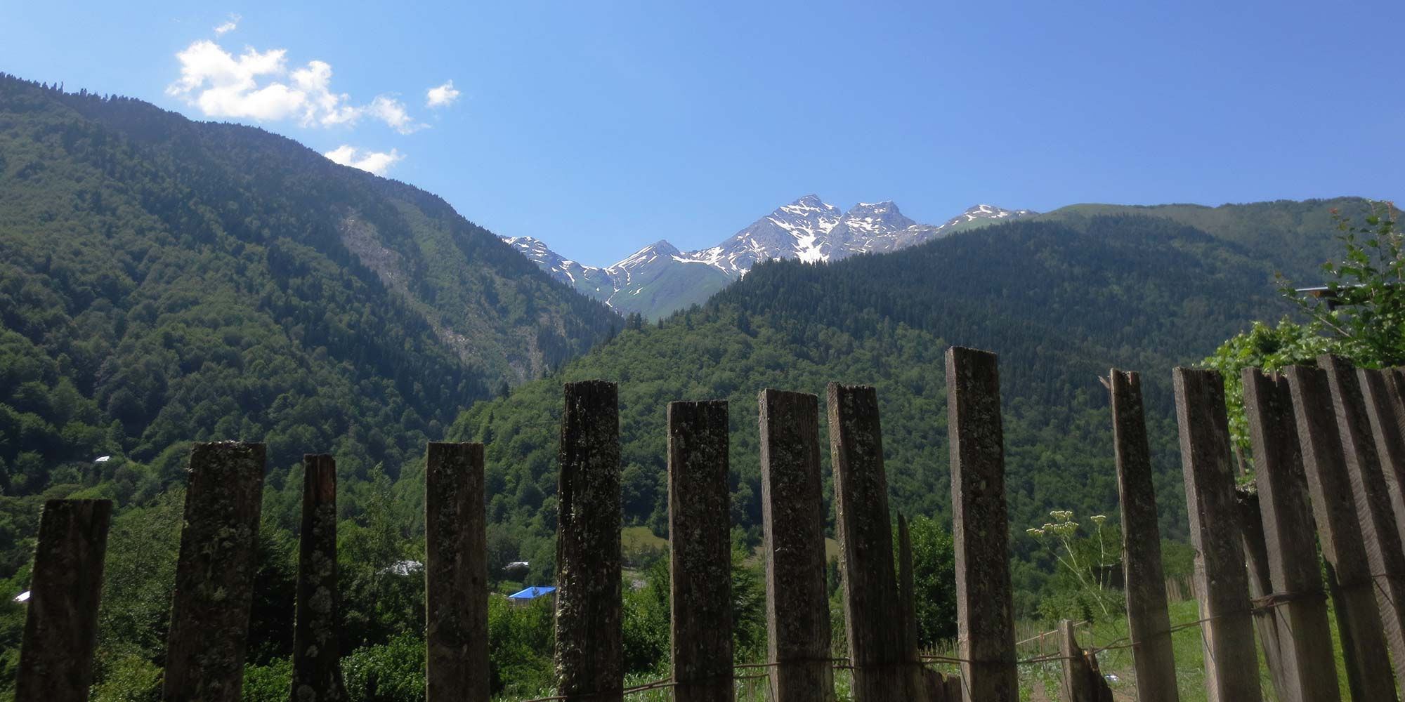 A mountain panorama seen from behind a raggedy wooden fence.