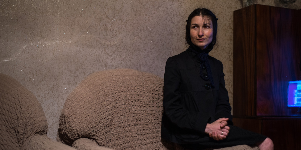 A woman dressed in black, sitting on a couch in dimmed light.