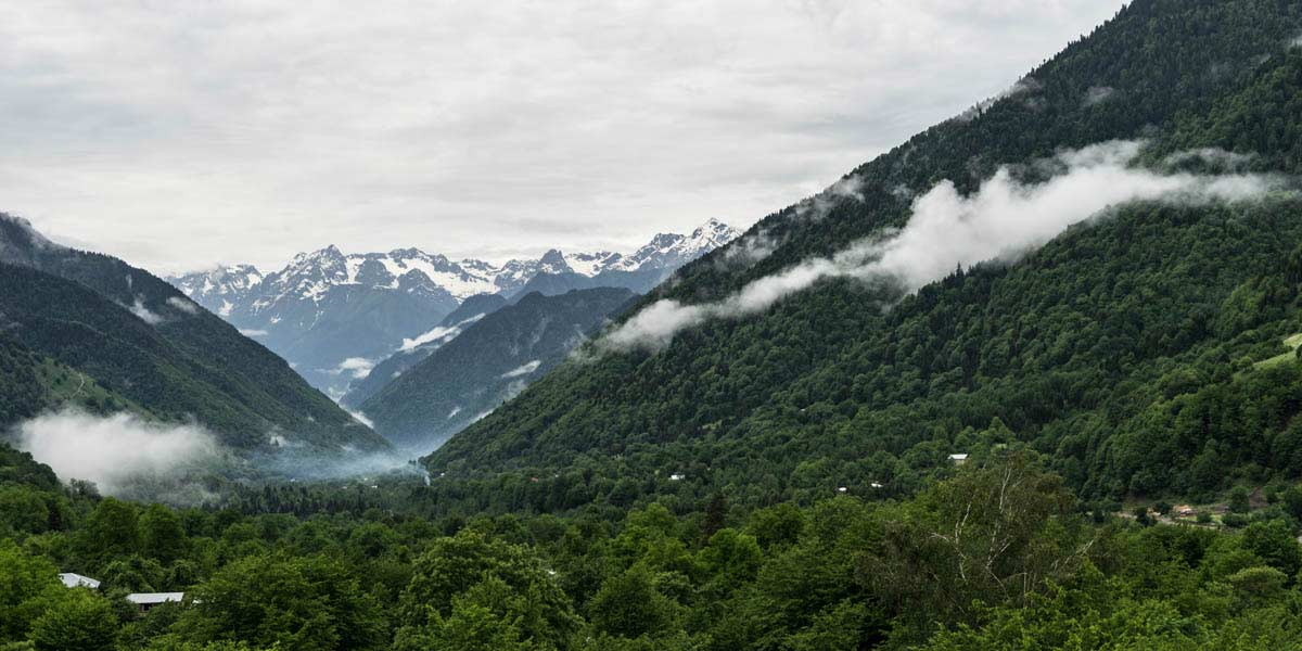 A parnoama view of lush green mountains and snow-covered peaks in the distance.