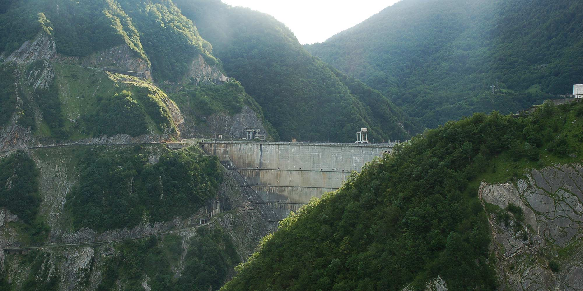A dam construction visible between tall green mountains in Georgia.