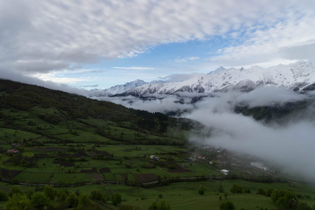 Mountains, meadows and a town covered in fog, seen in a panoramic view.