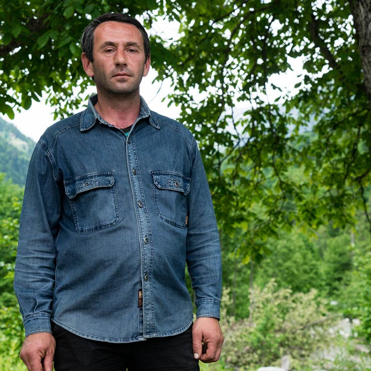 Image of Giorgi with trees and beautiful Svaneti landscape at the background.
