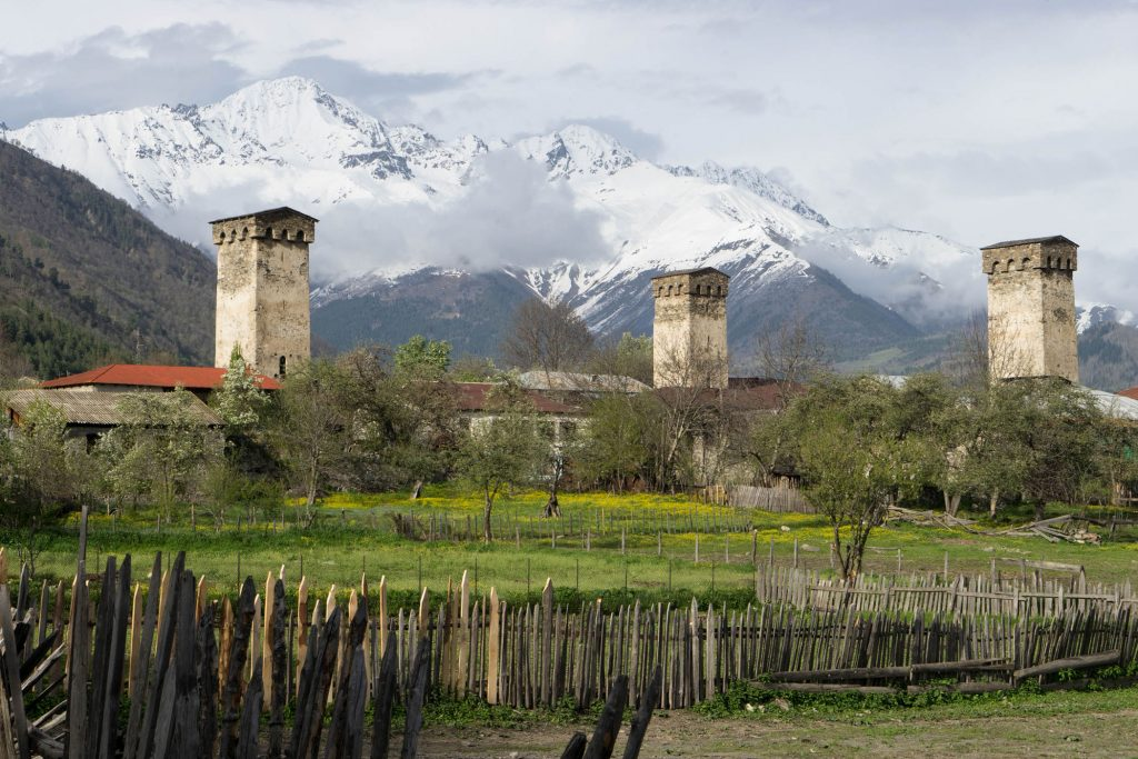 A view of stone towers and snowy mountain peaks in the distance.
