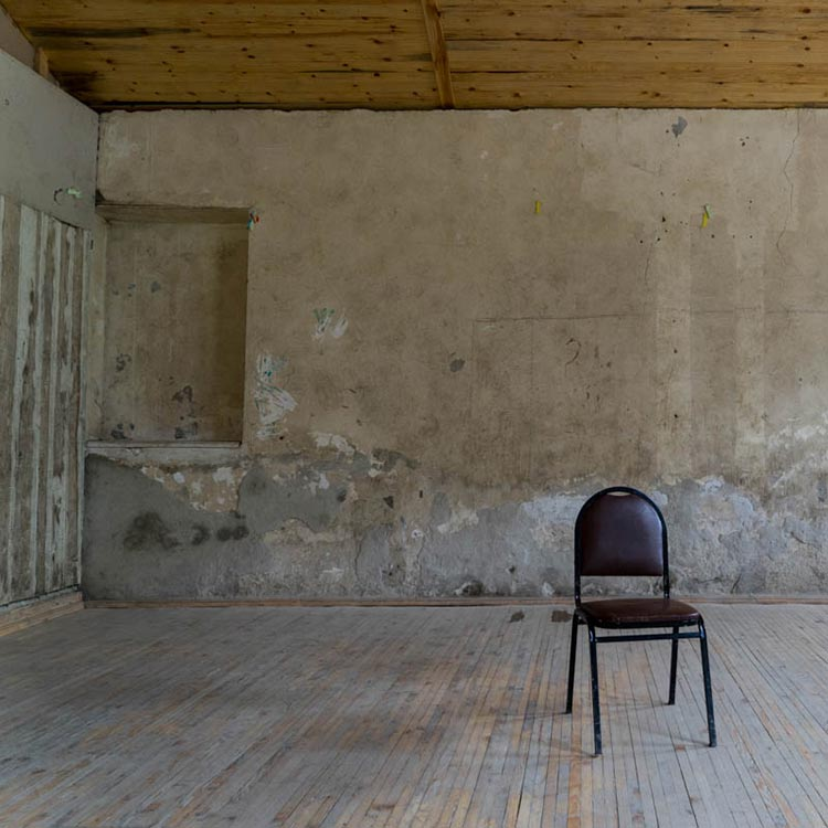 The image of an destroyed empty room with the chair in the middle