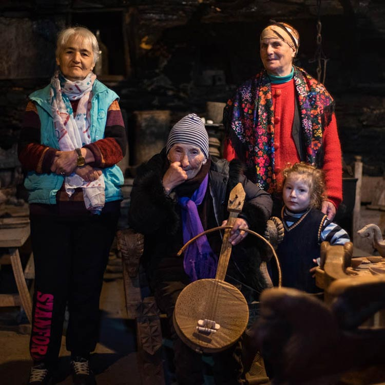 Image of Group members, three old ladies, with little girl beside and an traditional Svan musical instrument.