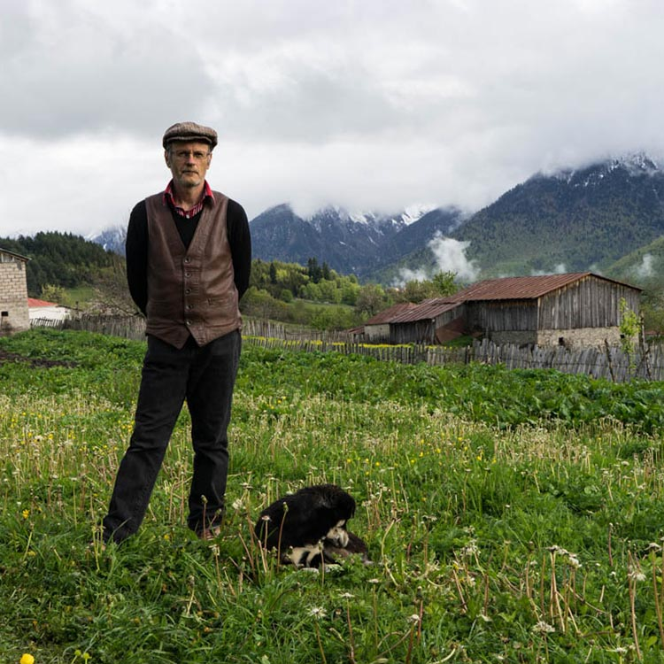 Tony and his dog in the yard of his house with the beautiful Svaneti landscape at the background
