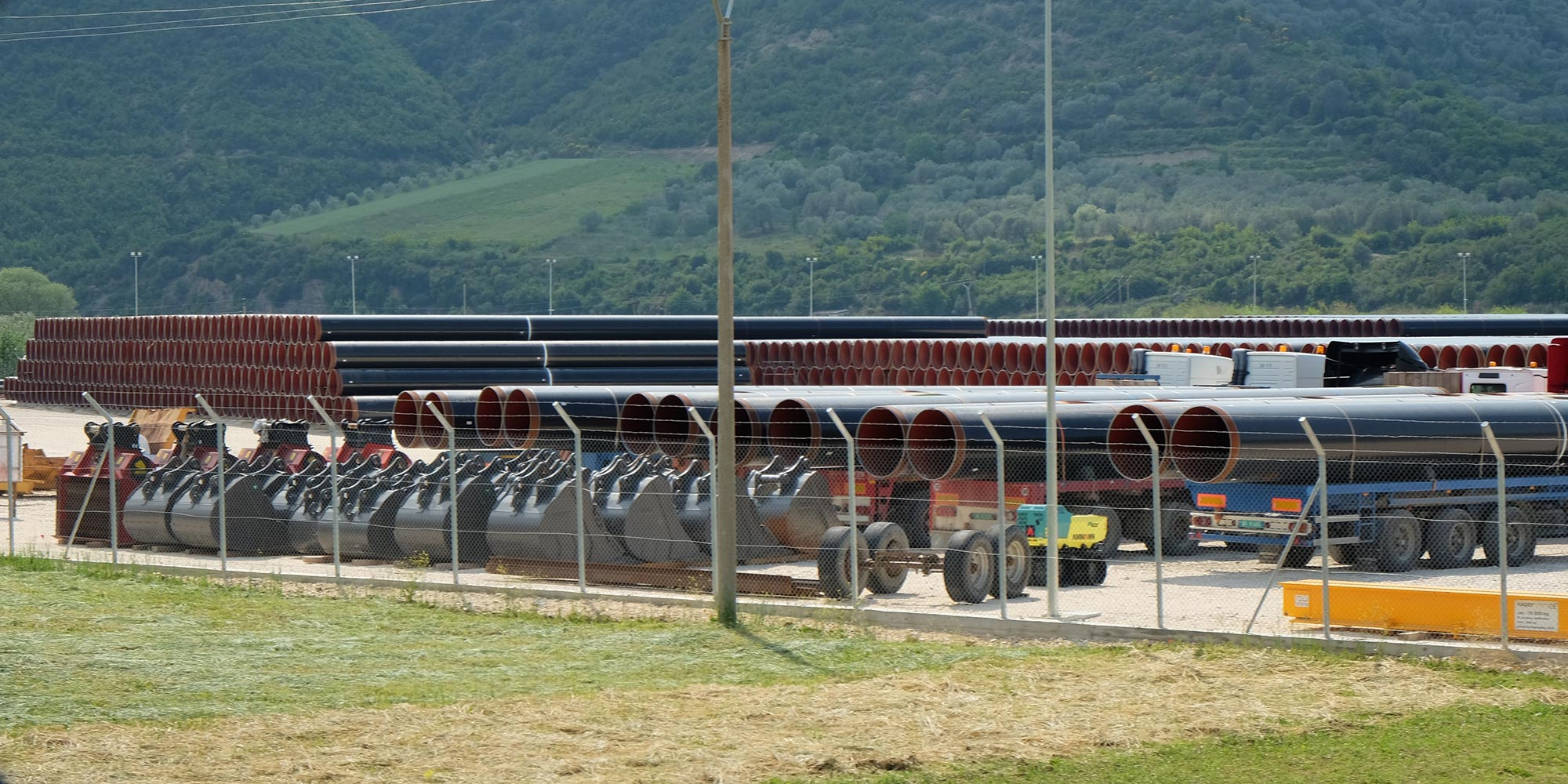 Black pipes for the Trans-Adriatic Pipeline are lying in a fenced area.