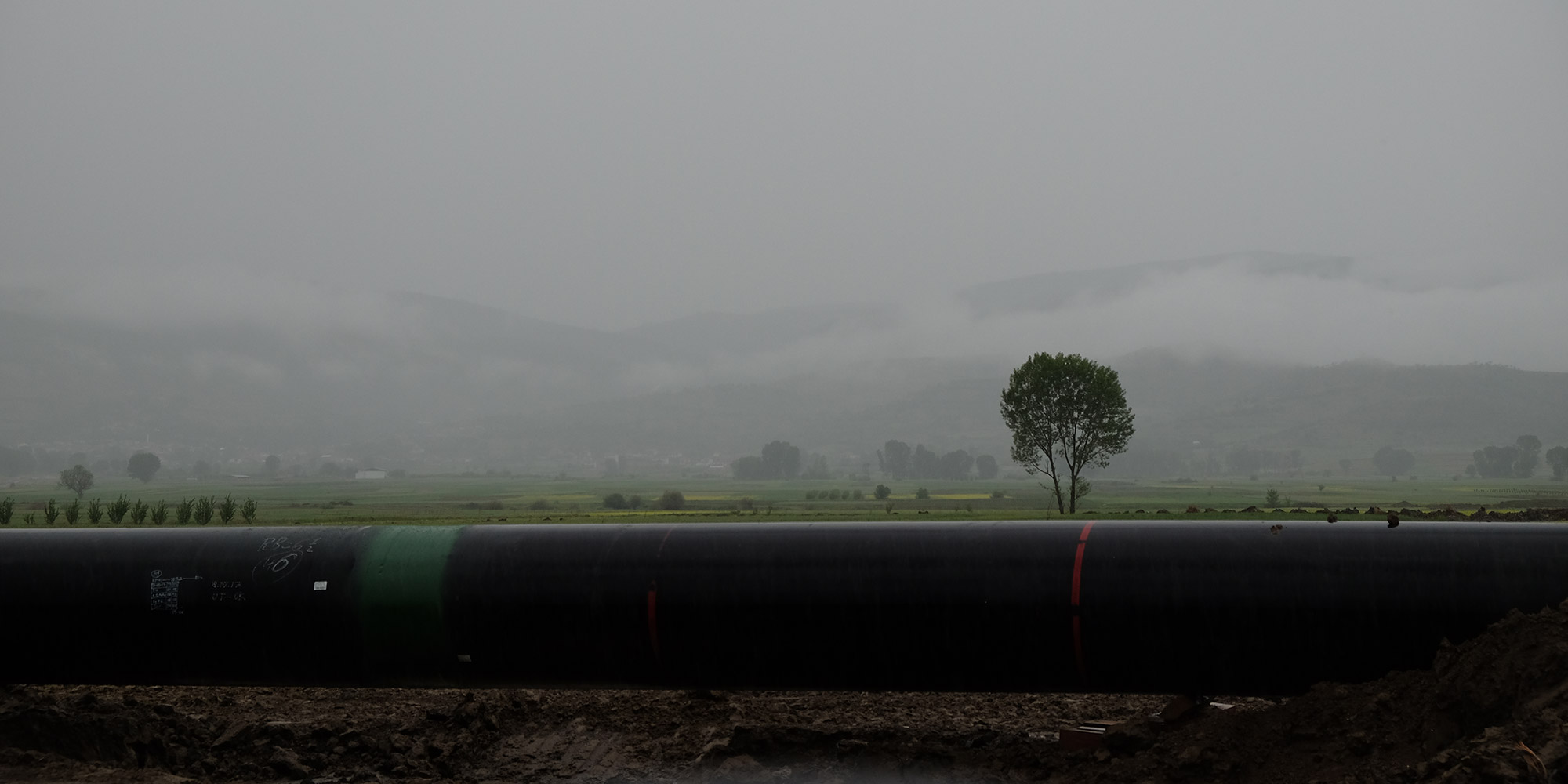 A black pipe in front of a foggy panorama.