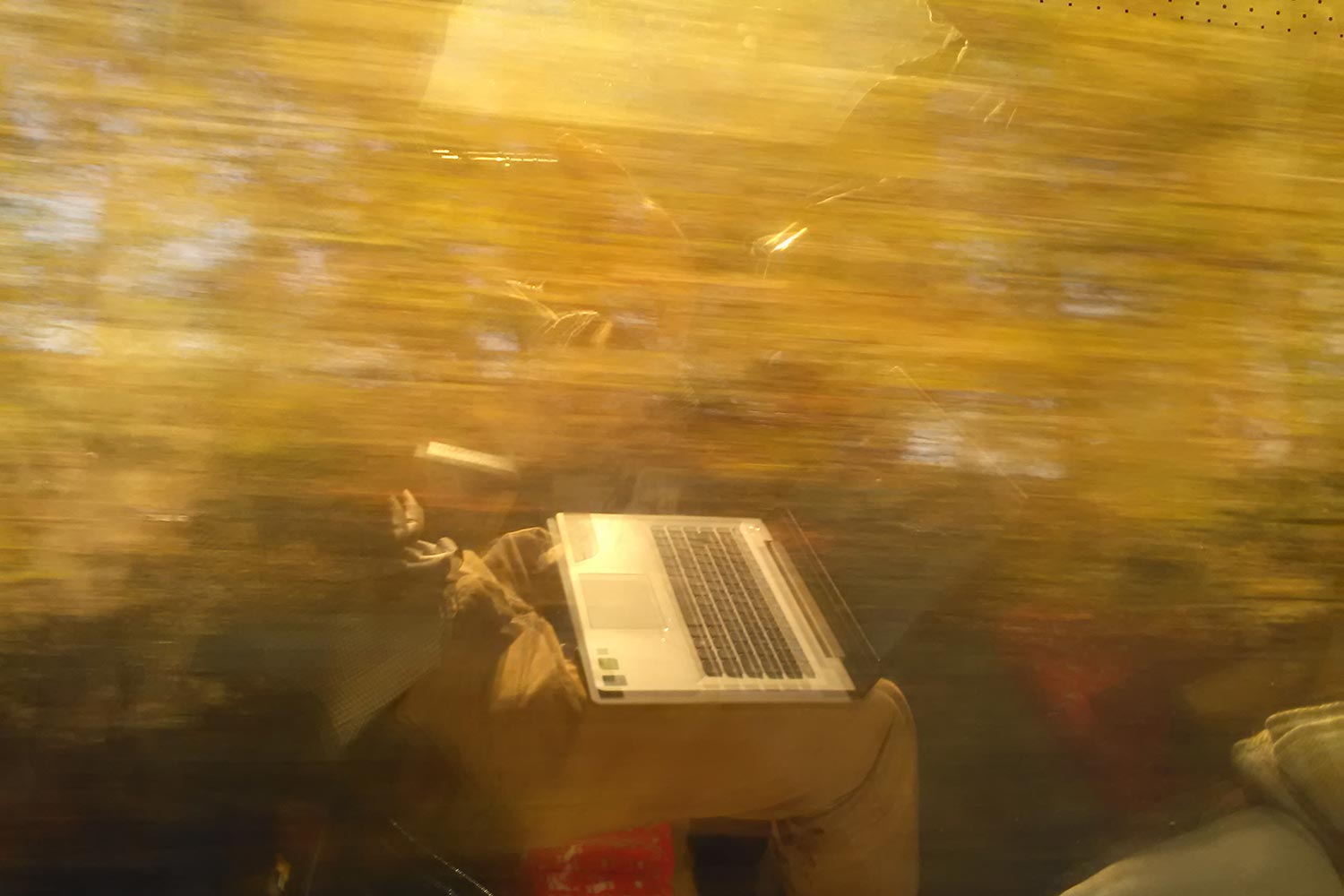 Image: A blurred reflection of a person with a laptop.